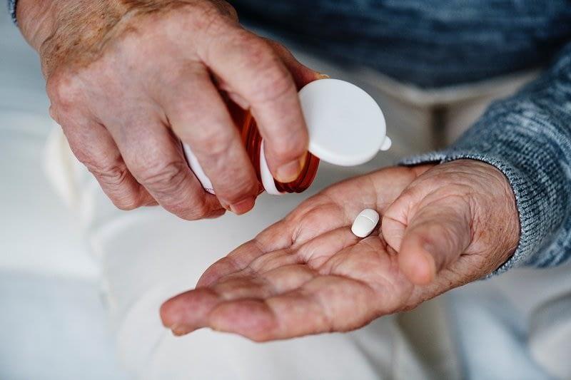 starszy pan z tabletką 